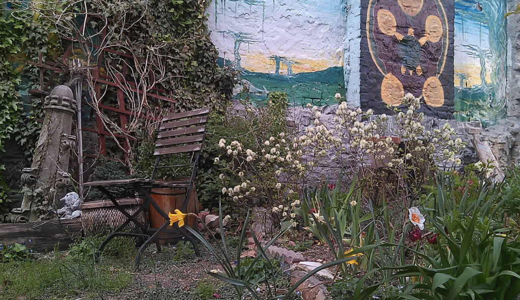 Bench, flowers, and mural in Bushwick's Eldert Street Garden