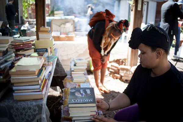 A woman arranges books at The Free Black Women's Library, hosted by 462 Halsey Community Garden on Mothers' Day