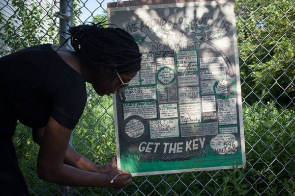 East NY Farms! extern Faith Titilawo hangs sign on fence