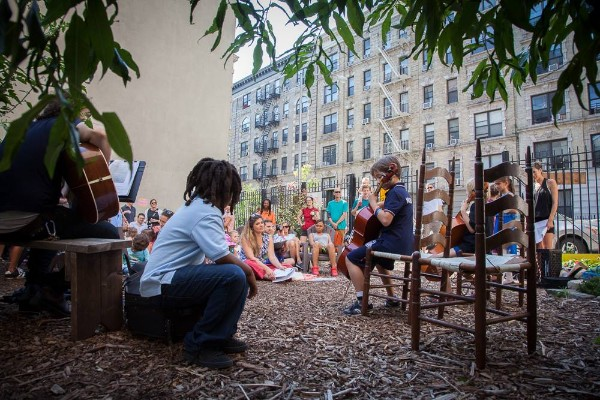 A child plays the violin for an audience in Electric Ladybug Garden in Harlem (photo copyright Murray Cox)