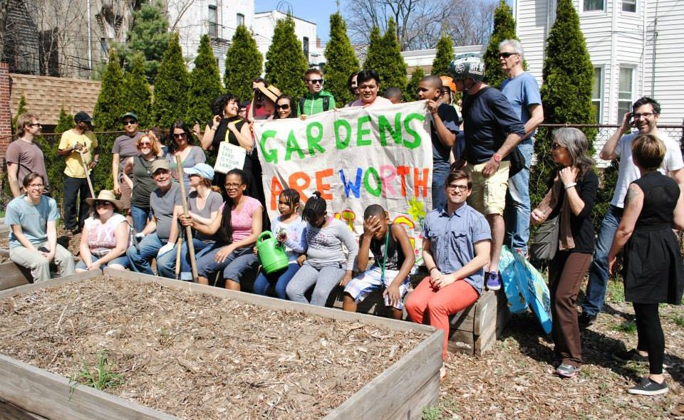 "Supporters of Maple Street Garden hold up a sign at Maple Street Garden: ""Gardens are worth Saving!"""