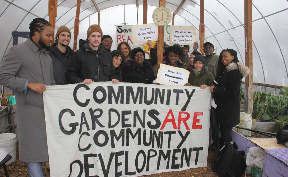 "Gardeners hold sign that reads ""Community Gardens are Community Development"""