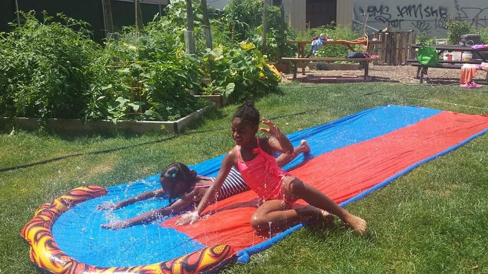 Two kids enjoy a Slip 'N Slide at Patchen Community Square